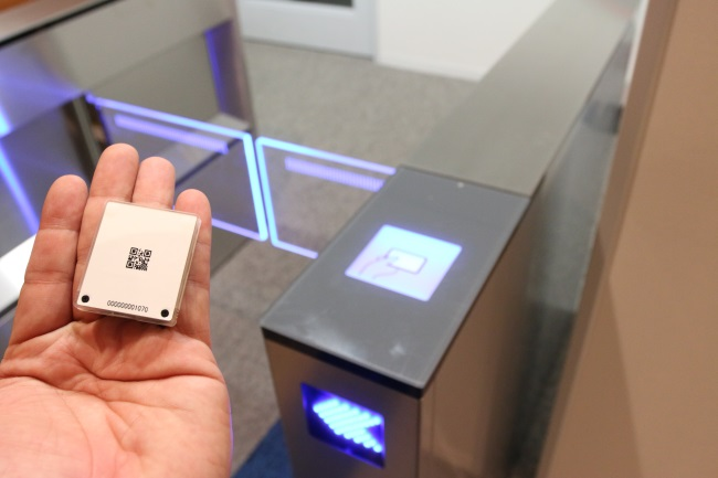 IoT関連の特許技術の1つ「電界通信」を使ったタッチタグ。現状はサンプル用のサイズだが、量産化後にはさらなる小型化も可能だという。従来のICカード認証とは異なる手軽さを強みに普及を目指している